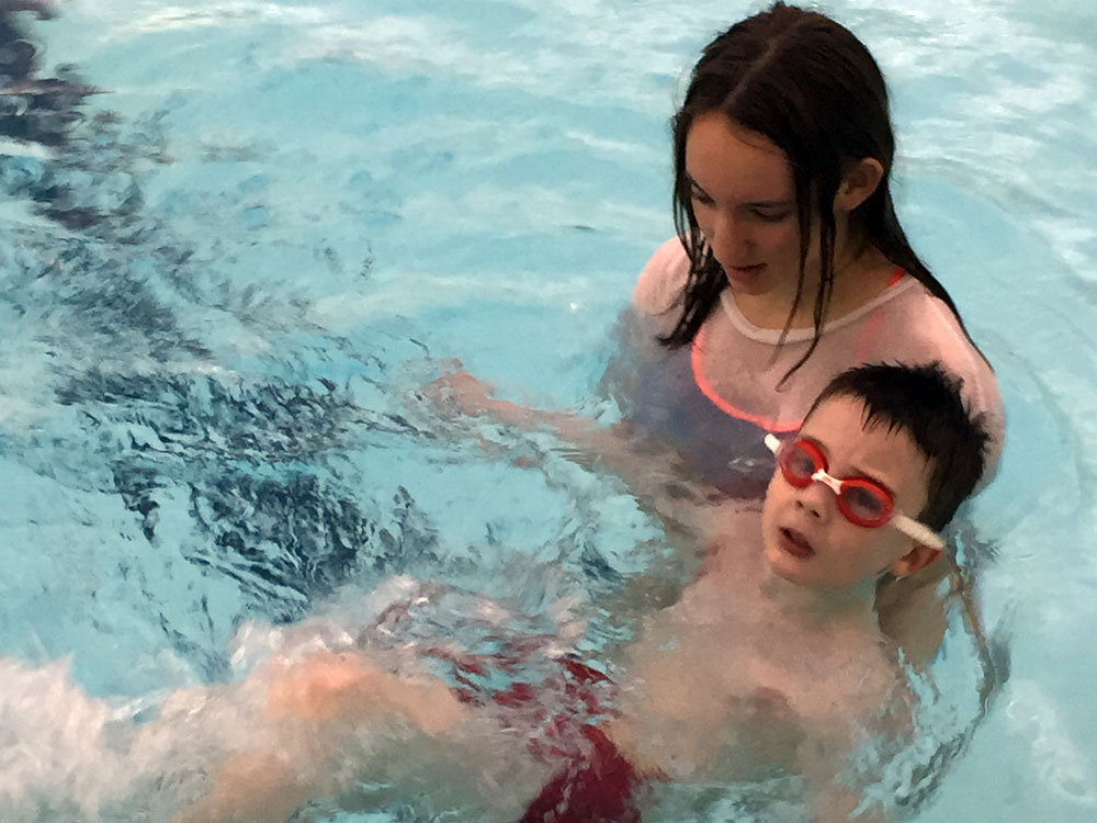 Female swimming helper and pupil